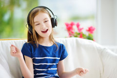 Cute girl wearing huge wireless headphones. Pretty child listening to the music. Schoolgirl having fun listening to kid`s songs at Stock Photography