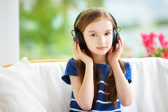 Cute girl wearing huge wireless headphones. Pretty child listening to the music. Schoolgirl having fun listening to kid`s songs at Stock Photos