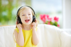 Cute girl wearing huge wireless headphones. Pretty child listening to the music. Schoolgirl having fun listening to kid`s songs at Royalty Free Stock Photos
