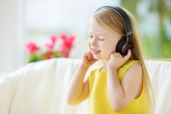 Cute girl wearing huge wireless headphones. Pretty child listening to the music. Schoolgirl having fun listening to kid`s songs at Stock Photo