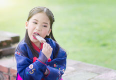 Cute girl wearing Japaness costumes eating ice-cream Royalty Free Stock Photography