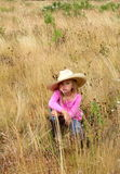 Cute girl wearing a large hat. A sober little 6 year old girl with blond hair wearing a cowboy hat sitting in tall grass wearing pink shirt. Shallow depth of Royalty Free Stock Photos