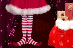 Cute girl wearing red white striped elf stockings and a cute dress standing next to a santa claus bag full of presents on a stock photo