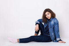 A cute girl wearing stylish jean clothes sitting on the floor indoors isolated over white background looking into camera with her Royalty Free Stock Image