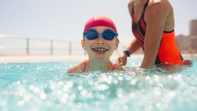 Girl getting swimming lesson in the pool. Cute girl wearing swim cap and goggles learning to swim with mothers help in a pool. Girl having swimming lesson in the royalty free stock photo