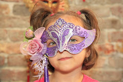 Cute girl wearing traditional Venetian mask. With brick wall in the background Stock Photos