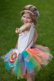 Cute girl wearing tutu and colored rim, pointing with her finger. Stock Photography