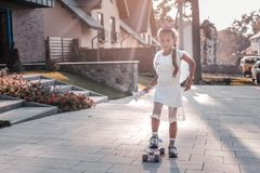 Cute girl wearing white dress and little crown standing on her skateboard stock photography