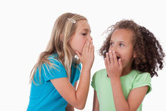 Cute girl whispering a secret to her friend Stock Image