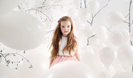 Cute girl among white balloons Royalty Free Stock Image
