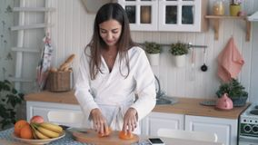 Cute girl in white bathrobe cuts orange on board in kitchen, slow motion. Concept morning time, vegetarian stock footage