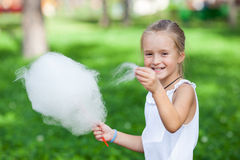 Cute girl with white cotton candy. In the summer park Stock Photo