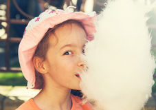 Cute girl with white cotton candy. Toned Stock Photo