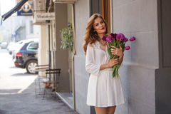 Cute girl in white dress and a  beautiful bouquet of tulips. Stock Images