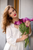 Cute girl in white dress and a  beautiful bouquet of tulips. Royalty Free Stock Image