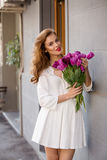 Cute girl in white dress and a  beautiful bouquet of tulips. Royalty Free Stock Photos