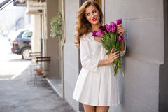 Cute girl in white dress and a  beautiful bouquet of tulips. Stock Image
