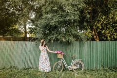 Cute girl in white-flower dress and hat is standing near green fence and trees. Her white vintage bicycle with bag of. Cute brunnete girl in white-flower dress Royalty Free Stock Photos