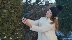Cute girl in white fur coat makes a selfie at fir-tree background stock video