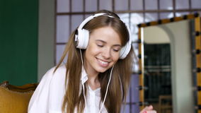 Cute girl with white headphone dances in the room stock video