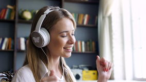 Cute girl with white headphone dances in the room stock video footage