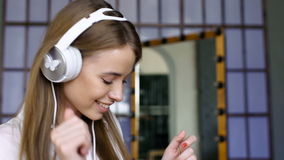 Cute girl with white headphone dances in the room stock footage