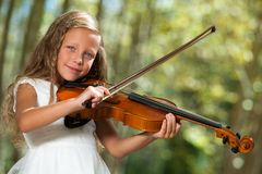 Cute girl in white playing violin outdoors. Royalty Free Stock Photography