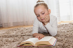 Cute girl who reads a book on living room floor Royalty Free Stock Images
