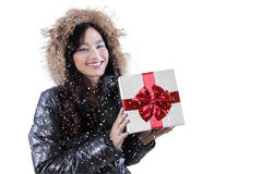 Cute girl with winter clothes holding presents. Attractive teenage girl holding presents in the studio while wearing winter jacket and smiling happy Stock Photo