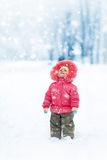 Cute girl winter portrait. Looking at falling snowflakes Royalty Free Stock Photography