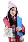 Cute girl in winter wear offering money Royalty Free Stock Photo