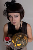 Cute girl - witch with skull and a pumpkin Royalty Free Stock Photography