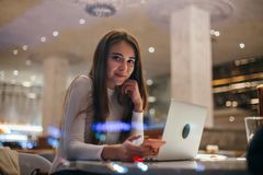 Cute girl works on laptop in hipster cafe royalty free stock photo