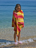 Cute girl wrapped in towel standing in the sea Stock Photos
