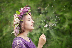 Cute girl in a wreath of lilacs blowing on a dandelion Stock Image