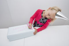 Cute girl writing on birthday gift at table in house Royalty Free Stock Photo
