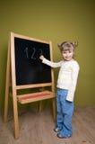 Cute girl writing on blackboard Stock Image