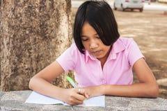 Cute girl writing book Stock Photo