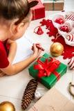 Cute girl writing letter to Santa on livingroom floor. Young girl writing her wishlist. Cute girl writing letter to Santa on livingroom floor. Young girl stock images