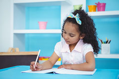 Cute girl writing on notebook Stock Images