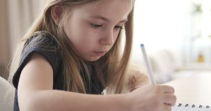 Cute girl writing with pen. Adorable girl writing with pen doing her homework stock video footage