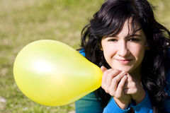 Cute girl with yellow colored balloon Stock Photos