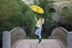 Cute girl in yellow shirt and jeans walking on the bridge with a bright umbrella at the evening royalty free stock image