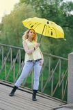Cute girl in yellow shirt and jeans walking on the bridge with a bright umbrella at the evening stock photos