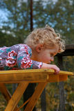 Cute Girl on Yellow Table. A cute little girl laying across a yellow table Stock Photography