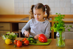 Cute girl of younger school age cuts vegetables and greens for salad. Salad bowl is already full, but little cook still cuts some broccoli. Kitchen is purely stock photography