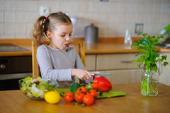 Cute girl of younger school age cuts vegetables and greens for salad. Salad bowl is already full, but little cook still cuts some red paprika . Kitchen is royalty free stock photo