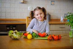 Cute girl of younger school age cuts vegetables and greens for salad. Salad bowl is already full, but little cook still cuts some red paprika . Kitchen is royalty free stock photos