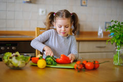 Cute girl of younger school age cuts vegetables and greens for salad. Salad bowl is already full, but little cook still cuts some red paprika . Kitchen is Stock Images