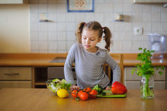 Cute girl of younger school age cuts vegetables and greens for salad. Stock Photography